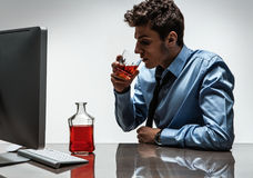 Young alcoholic man drinking whiskey sitting drunk at office with computer Stock Photo