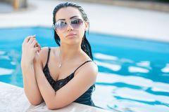 Young alluring brunette. With glasses posing in the pool dressed in black dress stock photography