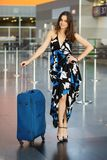 Young alluring brunette. Posing at the airport standing next to a suitcase dressed in a long dress royalty free stock images