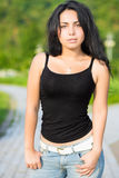 Young alluring brunette. Posing in black t-shirt and blue jeans outdoors Stock Photos