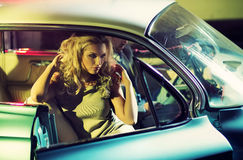 Young alluring couple in the retro car. Young alluring couple in the shiny retro car Stock Photo