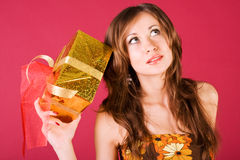 Young alluring girl in dress with a present Royalty Free Stock Image
