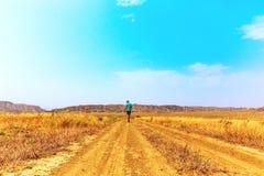 Young alone traveler guy walks wandering on hot savannah. Travel lifestyle. Young traveler guy walks wandering on hot savannah stock photo