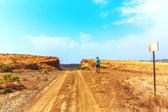 Young alone traveler guy walks wandering on hot savannah. Travel lifestyle. Young traveler guy walks wandering on hot savannah royalty free stock images