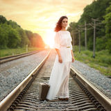 Young alone woman standing with suitcase on railroad Stock Photos