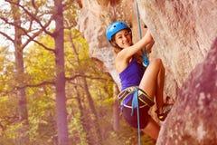 Young alpinist girl climbing on a mountain rock. Young girl climbing on a mountain rock wearing alpinist equipment stock photos