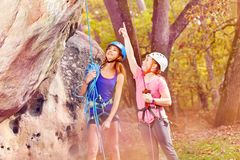 Young alpinist showing directions in forest area. Young alpinist showing directions, mountaineers tourists climbing mountain in forest area Stock Photos