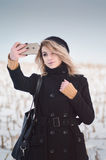 Young alternative girl taking selfie in the snowy field. Young blond alternative girl in black clothes taking selfie in the snowy field Royalty Free Stock Photos