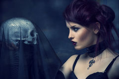 Young alternative woman with a skull. Stock Images