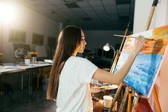 Woman artist painting a picture on easel with oil paints in her workshop Royalty Free Stock Photo