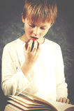 Young amazed boy reading a book with red healthy apple in his ha Royalty Free Stock Images