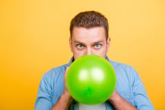 Young, amazed, stylish blond man is blowing green balloon for bi. Rthday party and looking at the camera with wide open eyes over yellow background Royalty Free Stock Photo