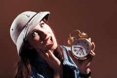 Young amazed woman in pith helmet holding alarm clock Stock Photography