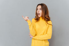 Young amazed woman in yellow sweater pointing finger away Royalty Free Stock Image