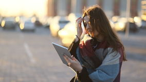 Young amazing urban girl with brown hair and tablet in sunset, smiling and laughting stock footage