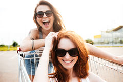 Young amazing women friends have fun with shopping trolleys. Picture of young amazing women friends have fun with shopping trolleys Stock Photos