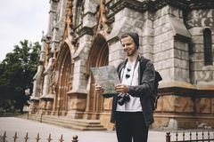Young and ambitious tourist is standing on the sidewalk near the cathedral and reading a map. The guy was lost but now he has finally found his current Royalty Free Stock Photo