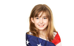 Young American. Pretty young child wrapped in a American Flag Stock Image