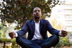 Young american african businessman in informal clothes meditating in lotus pose taking a deep breath outside corporate. Office.Business yoga and stress free stock photo