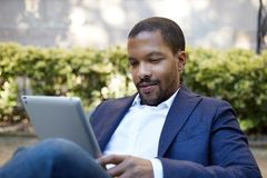 Young american african businessman in informal clothes working at sunny street on electronic touch pad,checking e-mail. Using Internet-enabled electronic device Royalty Free Stock Photo