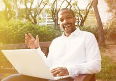 Young american african businessman in informal clothes working at sunny street on laptop,checking e-mail. Blurred. Background Stock Image