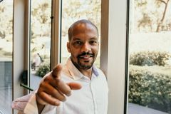 Young american african confident businessman in white shirt pointing hand to camera and smiling inside corporate office stock photo