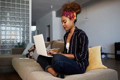 Young american african female blogger working remotely on digital netbook with internet text. African woman copywriter. Typing article for website on keyboard royalty free stock image