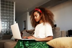 Young american african woman typing on laptop, texting friends via social networks. Student girl browsing Internet. Using wi-fi, sitting on sofa at home stock image