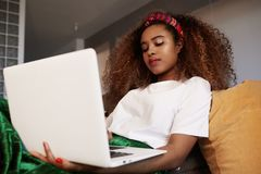 Young american african woman using laptop, texting friends via social networks. Student girl browsing Internet, using wi. Fi, sitting on sofa at home royalty free stock photography