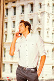 Young American Businessman talking on cell phone outside. Young Businessman Calling Outside. Wearing a white shirt, black pants, a young college student is Royalty Free Stock Images