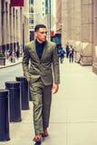 Young American businessman traveling in New York. Wearing green suit, black undershirt, brown leather shoes, walking on sidewalk of vintage street, looking Royalty Free Stock Images