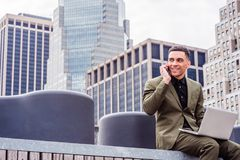 Young American Businessman traveling, working in New York,. Wearing green suit, siting at street park in business district with high building, working on laptop Stock Image