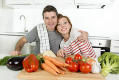 Young American couple working at home kitchen preparing vegetable salad together smiling happy Royalty Free Stock Photos