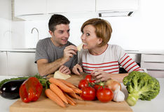 Young American couple working at home kitchen preparing vegetable salad together smiling happy Stock Images