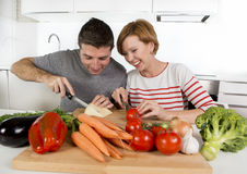 Young American couple working at home kitchen preparing vegetable salad together smiling happy. Young beautiful American couple working at home kitchen Stock Images