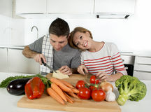 Young American couple working at home kitchen preparing vegetable salad together smiling happy Stock Photos
