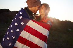 Young American Explorers. Portrait of young tourist couple standing close together in mountains, embracing tenderly wrapped in American flag at sunset Royalty Free Stock Images
