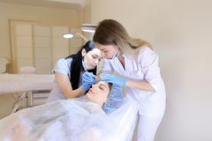 Young american female person visiting cosmetologist and nurse for tattooing eyebrows by pen. royalty free stock photo