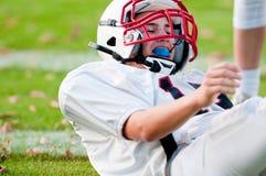 American football boy on ground Royalty Free Stock Photo