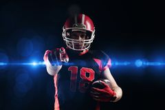 American football player in helmet holding rugby ball and pointing. Young American football player in helmet holding rugby ball and pointing royalty free stock images