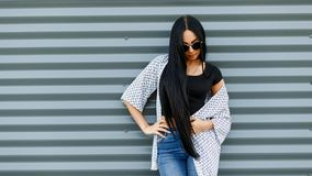 Young American hipster woman with long hair in round sunglasses in a black fashionable top in a light summer jacket. In vintage jeans is standing near a gray stock photography