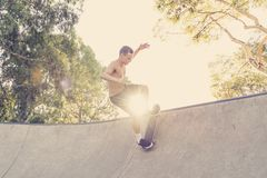 Young American man in naked torso practicing radical skate board jumping and enjoying tricks and stunts in concrete half pipe skat. Ing track in sport and stock image
