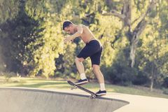 Young American man in naked torso practicing radical skate board jumping and enjoying tricks and stunts in concrete half pipe skat. Ing track in sport and royalty free stock images
