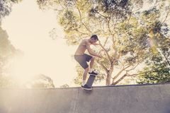 Young American man in naked torso practicing radical skate board jumping and enjoying tricks and stunts in concrete half pipe skat. Ing track in sport and stock photo
