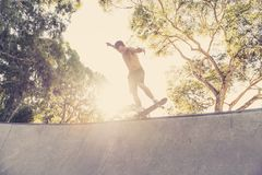 Young American man in naked torso practicing radical skate board jumping and enjoying tricks and stunts in concrete half pipe skat. Ing track in sport and royalty free stock photography