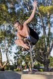 Young American man in naked torso practicing radical skate board jumping and enjoying tricks and stunts in concrete half pipe skat. Ing track in sport and stock photos