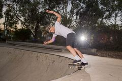 Young American man practicing radical skate board having fun enjoying tricks jumps and stunts in concrete half pipe skating track. In sport and healthy royalty free stock photo