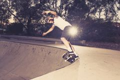 Young American man practicing radical skate board having fun enjoying tricks jumps and stunts in concrete half pipe skating track. In sport and healthy royalty free stock image