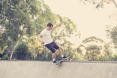 Man practicing radical skate board jumping and enjoying tricks and stunts in concrete half pipe skating track in sport and healthy. Young American man practicing royalty free stock photo