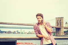 Young American man traveling in New York. Wearing red patterned shirt unbuttoned, white pullover undershirt, standing by East River, talking on cell phone Royalty Free Stock Photo